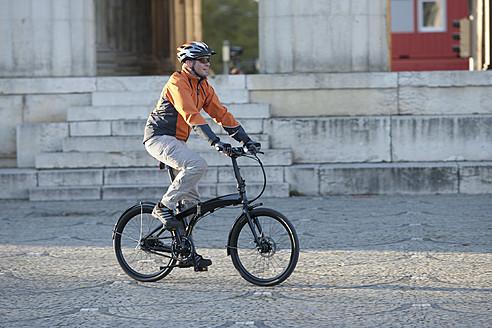 Germany, Bavaria, Munich, Mature man cycling through pavement - DSF000569