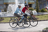 Italy, Trento, Man and woman cycling by fountain in Arco - DSF000575