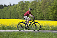 Germany, Bavaria, Starnberg, Mature man cycling through country road - DSF000577