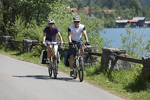 Germany, Bavaria, Man and woman cycling by Lake Walchensee - DSF000580