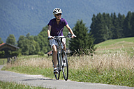 Germany, Bavaria, Young woman cycling through country road - DSF000607