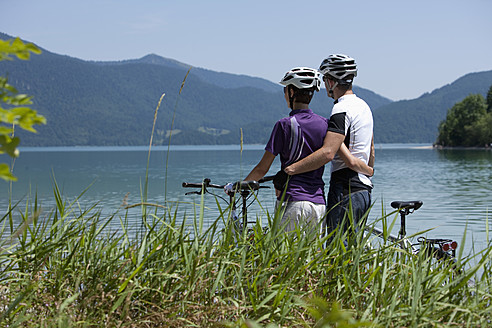 Germany, Bavaria, Man and woman with bike looking at Lake Walchensee - DSF000585