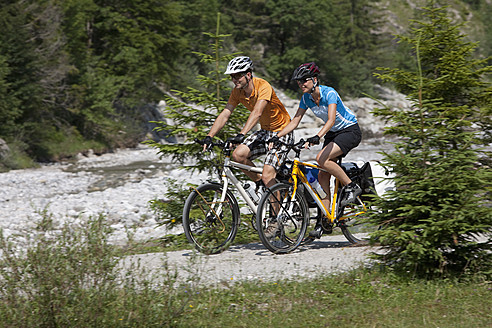 Austria, Tyrol, Eng, Man and woman cycling through dirt track - DSF000609
