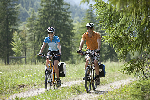 Austria, Tyrol, Man and woman cycling through dirt track - DSF000589