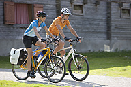 Austria, Tyrol, Man and woman cycling through road - DSF000592