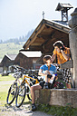 Austria, Tyrol, Man looking at woman filling water in bottle at water pump - DSF000611