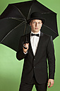 Young man holding umbrella against green background - MAEF004654