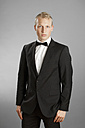 Young man in black suit against gray background - MAEF004657