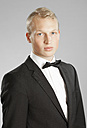 Young man in black suit against gray background - MAEF004658