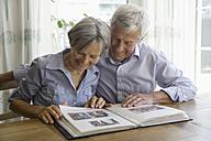 Germany, Bavaria, Senior couple with photo album, smiling - TCF002568