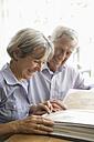 Germany, Bavaria, Senior couple with photo album, smiling - TCF002576