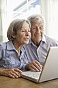 Germany, Bavaria, Senior couple using laptop at home - TCF002593