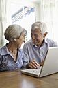 Germany, Bavaria, Senior couple using laptop at home, smiling - TCF002595