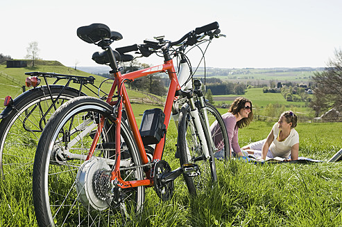 Germany, Bavaria, Mature women sitting on grass, electric bicycle in foreground - RNF000934