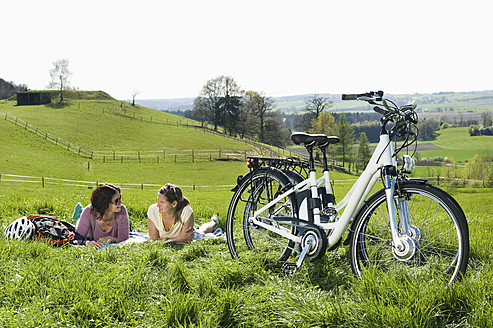 Germany, Bavaria, Mature women lying on grass, electric bicycle in foreground - RNF000936