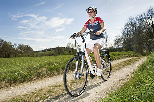 Germany, Bavaria, Mature woman riding electric bicycle - RNF000846