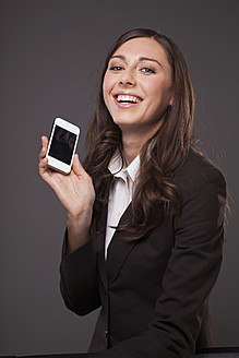 Businesswoman with mobile phone, smiling, portrait - PRAF000023