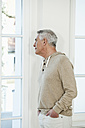 Germany, Berlin, Senior man looking through window - FMKYF000017