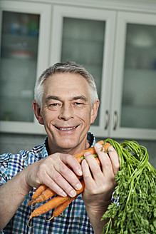 Germany, Berlin, Senior man holding carrots, portrait - FMKYF000029