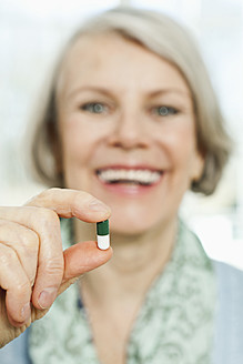Germany, Berlin, Senior woman holding pill, close up - FMKYF000062
