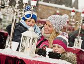 Austria, Salzburg, Mother with children at christmas market, smiling - HHF004196