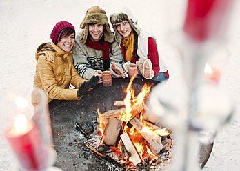 Austria, Salzburg, Man and women by fire at christmas market, smiling - HHF004210