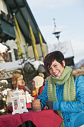 Austria, Salzburg, Young woman with cup, people in background - HHF004206
