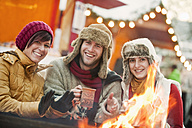 Austria, Salzburg, Man and women by fire at christmas market, smiling - HHF004204