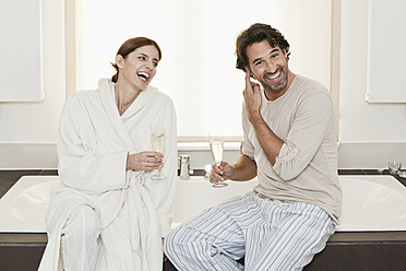 Germany, Berlin, Mature couple sitting on bathtub with sparkling wine - FMKYF000086