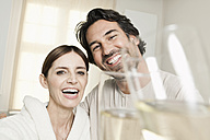 Germany, Berlin, Mature couple in bathroom with sparkling wine - FMKYF000092