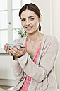 Germany, Berlin, Mature woman holding bowl, smiling, portrait - FMKYF000095