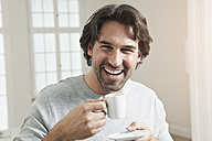 Germany, Berlin, Mature man with coffee cup, smiling, portrait - FMKYF000110