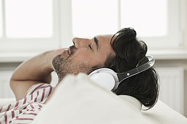 Germany, Berlin, Mature man listening music with head phones - FMKYF000119