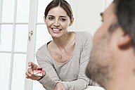 Germany, Berlin, Man looking at woman holding cake - FMKYF000125