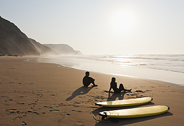 Portugal, Couple sitting on beach by surfboard - MIRF000461
