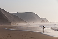 Portugal, Surfer walking on beach - MIRF000467
