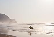 Portugal, Surfer walking on beach - MIRF000470