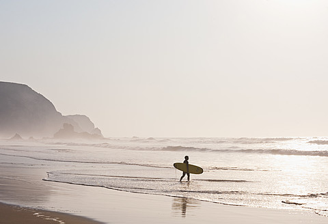 Portugal, Surfer walking on beach - MIRF000470