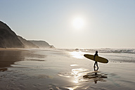 Portugal, Surfer walking on beach - MIRF000473