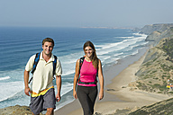 Portugal, Couple walking on beach - MIRF000479