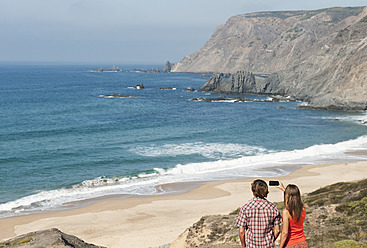 Portugal, Couple taking photograph at beach - MIRF000482