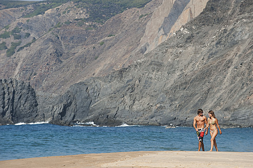 Portugal, Couple walking on beach - MIRF000485