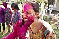 India, Ahmedabad, Man applying paint on woman face in Holi festival - MBE000359