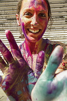 India, Ahmedabad, Young woman with colourfull hands and face on holi festival - MBEF000351