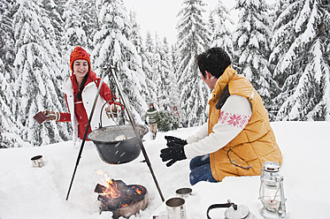 Austria, Salzburg, Man and woman by fireplace, people carrying christmas tree in background - HHF004229