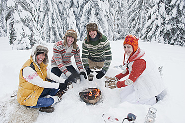 Austria, Salzburg, Men and women sitting at fire place in winter - HHF004218