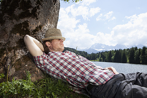 Germany, Bavaria, Mid adult man lying on grass under tree - RBF000909