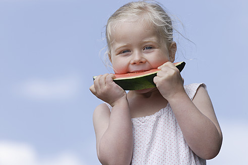 Germany, Bavaria, Girl eating piece of watermelon - TCF002774