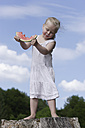 Germany, Bavaria, Girl standing eating piece of watermelon - TCF002771