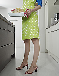 Germany, Cologne, Young woman with roasted chicken in kitchen - RHYF000110